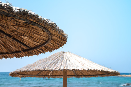 Photo for Two parasols against blue sky with sea in the background, selective focus, copy space. - Royalty Free Image