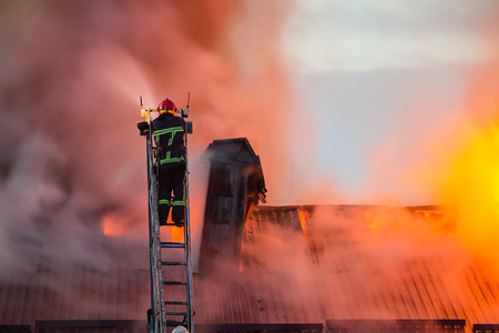 Foto de Firefighter or fireman on the ladder extinguishes burning fire flame with smoke on the apartment house roof. - Imagen libre de derechos