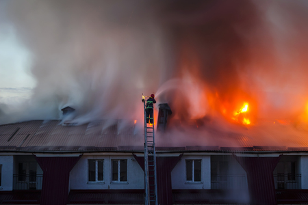 Foto de Burning fire flame with smoke on the apartment house roof in the city, firefighter or fireman on the ladder extinguishes fire. - Imagen libre de derechos
