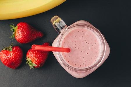 Photo for Smoothie with strawberry and banana in the jar at dark background, top view. - Royalty Free Image
