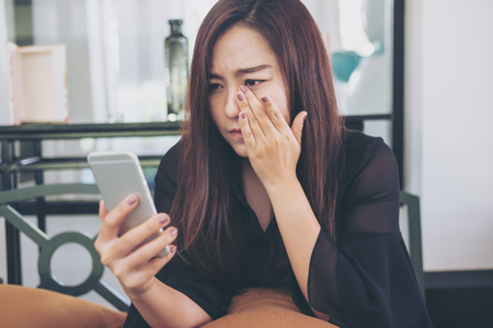 Photo pour A beautiful asian woman looking at smart phone with feeling sad and cry in cafe - image libre de droit