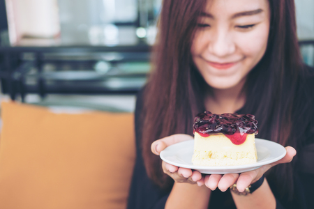 Photo for A beautiful asian woman holding  blueberry cheese cake  with feeling happy and good lifestyle in modern cafe - Royalty Free Image