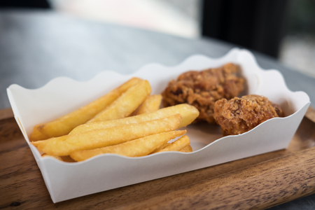 Photo for Closeup image of french fries and fried chicken in white paper plate with ketchup and chili sauce in plastic cups - Royalty Free Image