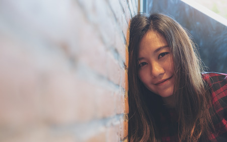 Photo for Closeup image of a smiley beautiful Asian woman leaning on brick wall in modern cafe - Royalty Free Image