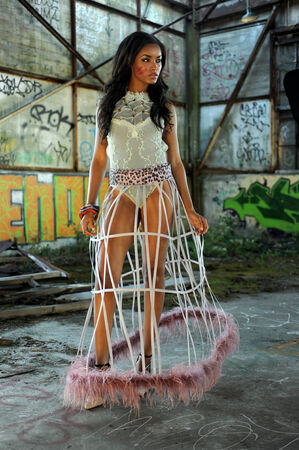 Attractive african american woman wearing swimgerie top and cage skirt at abandoned wearhouse background