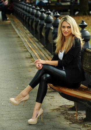 Photo pour Fashion glamour model posing on the bench at the autumn park. - image libre de droit