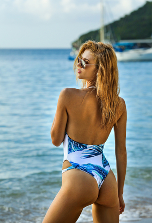 Foto de Beautiful young blonde woman in fashionable swimsuit posing on the beach in turning booty shows ass. Sexy model portrait with perfect body. Concept of summer vacation. - Imagen libre de derechos