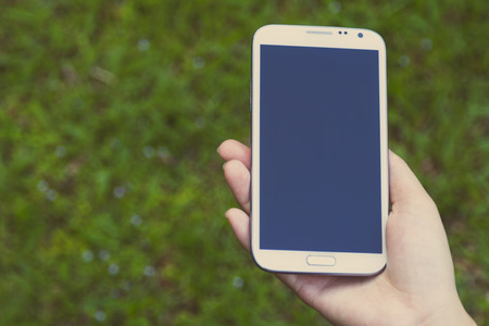 female hands using a smart phone, green nature background