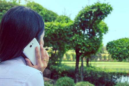 Closeup of female hands using a smart phone, green nature background