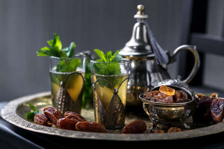 Photo for Moroccan tea with mint in traditional glasses, teapot and sugar - Royalty Free Image