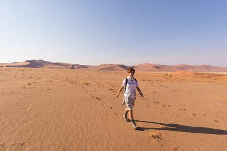 Photo for Tourist walking on the scenic dunes of Sossusvlei, Namib desert, Namib Naukluft National Park, Namibia. Adventure and exploration in Africa. - Royalty Free Image