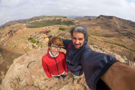 Foto de Couple selfie with outstretched arms, wind mountain summit, Golden Gate Highlands National Park, South Africa. Concept of adventure and traveling people. Fish eye view.  - Imagen libre de derechos