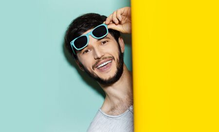 Foto de Studio portrait of young happy guy with blue shades on his head, comes out between two background of yellow and aqua menthe colors. - Imagen libre de derechos