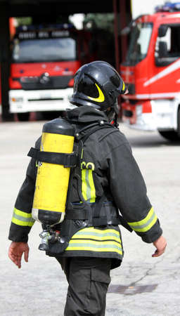 brave firefighter with yellow oxygen cylinder and the helmet walks towards the fire