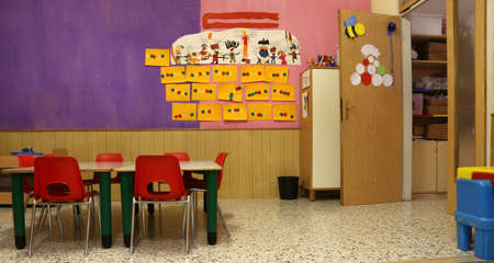 Photo pour Preschool classroom with red chairs and table with drawings of children hanging on the walls - image libre de droit