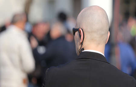Foto de bald security guard with the headset to control people - Imagen libre de derechos