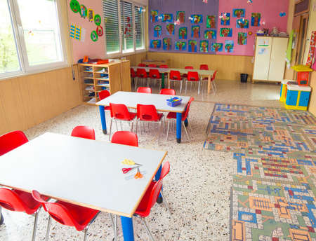 Foto de classromm of kindergarten with tables and small red chairs for children - Imagen libre de derechos