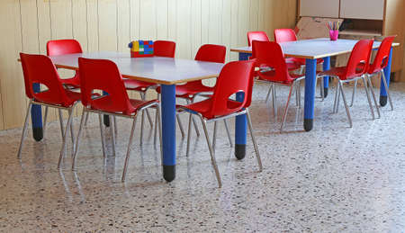 Foto de Red Chairs and tables in a kindergarten classroom - Imagen libre de derechos