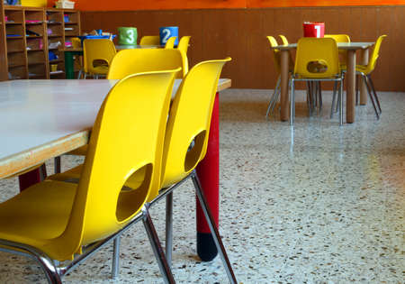 Photo for classroom of a nursery with the little yellow chairs and tables - Royalty Free Image