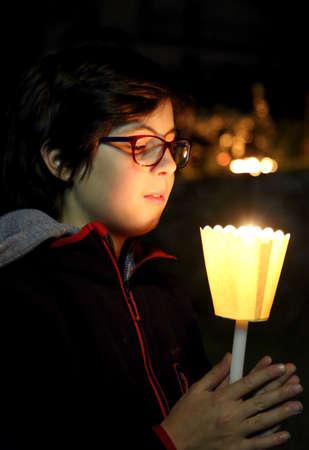 Photo pour Young caucasian boy with candle during a relgion mass outdoor - image libre de droit