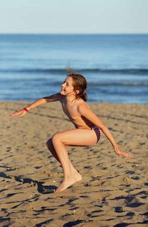 Foto de pretty girl with swimsuit on the beach makes a great leap of joy - Imagen libre de derechos