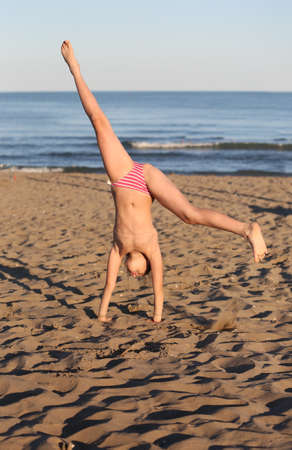 Foto de pretty girl with swimsuit on the beach makes the headrest with her legs in the air - Imagen libre de derechos