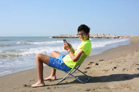 Photo pour smiling caucasian boy reads an ebook sitting on the beach chair at the seashore in summer with a fluorescent t-shirt - image libre de droit