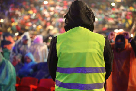 Photo for Security guard with safety vest controls people during an important event while it is raining - Royalty Free Image