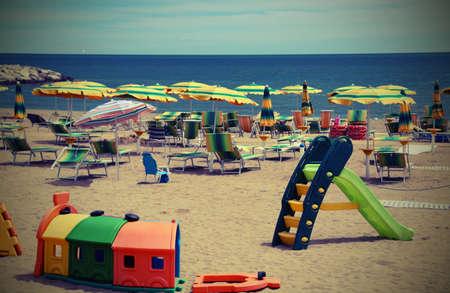 Foto de playground on the sea beach in summer with many sun umbrellas and vintage efffect - Imagen libre de derechos