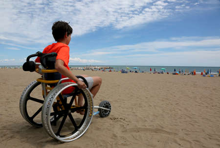 Photo pour hopeful boy looks at the sea from the wheelchair at the beach - image libre de droit