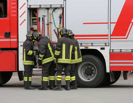 Photo pour firefighters sort the water pipes near the fire truck - image libre de droit