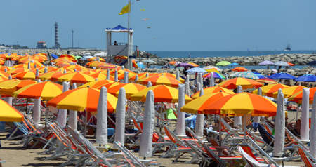 Foto de Cavallino Treporti, VE, Italy - July 12, 2015: beach with umbrellas and deck chairs for tanning and the turret of the surveillance and rescue service - Imagen libre de derechos