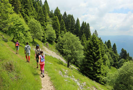 Photo pour family of four walks on the path in mountains - image libre de droit