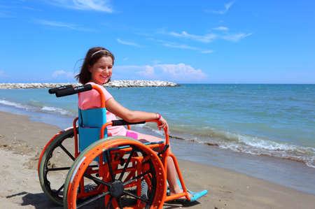Foto de caucasian little girl on the wheelchair on summer by the sea - Imagen libre de derechos