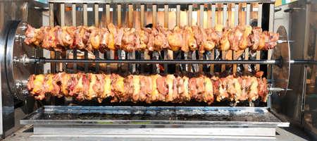 Foto de large skewers of chicken and pork meat while cooking very slowly in the big roaster - Imagen libre de derechos