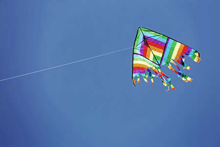 Foto de Multcolored kite on the blue sky with old toned effect - Imagen libre de derechos