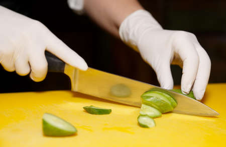 Photo pour Chef is cutting cucumber on yellow plank - image libre de droit