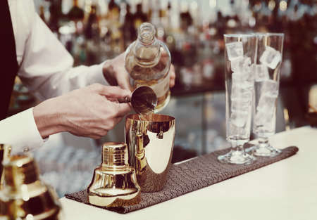 Photo for Bartender is pouring liquor in golden shaker, toned image - Royalty Free Image