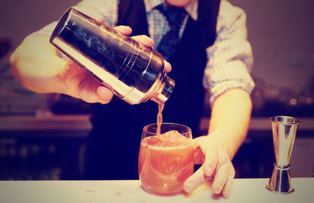 Photo for Bartender is making cocktail at bar counter, toned image - Royalty Free Image