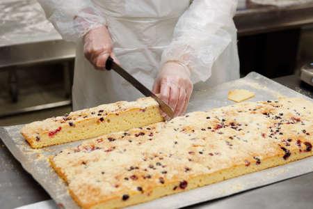 Foto de Female pastry chef chef is cutting biscuit in professional kitchen - Imagen libre de derechos