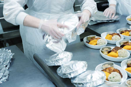 Photo pour Chef is wrapping airline food in foil, professional kitchen, toned image - image libre de droit