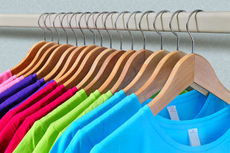 Photo for Pink, purple, crimson, bright green and turquoise women's T-shirts hanging on wooden hangers on gray background - Royalty Free Image