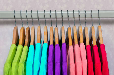 Photo for Pink, purple, crimson, bright green and turquoise women's T-shirts hanging on wooden hangers on light background. Side view. - Royalty Free Image