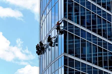 Photo pour Industrial climbers wash the front windows of a modern skyscraper - image libre de droit