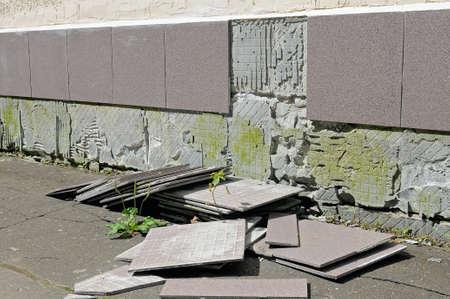 Foto de Construction defect: poorly made work of builders, tiles fell off the wall of the house - Imagen libre de derechos