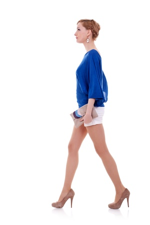 young confident woman is walking. She is smiling and looking away from the camera isolated over white background