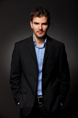 Photo for handsome business man standing with hands in pockets against dark background - Royalty Free Image