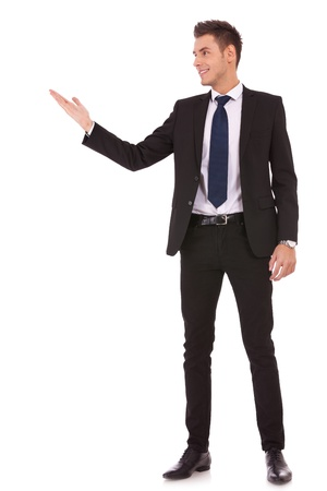 Attractive business man shows you copy space on white background