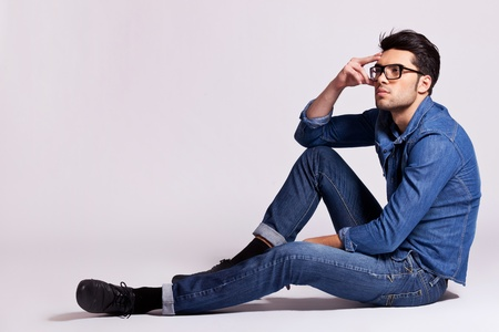 Foto de side view of a casual fashion man sitting on gray background and looking away from the camera - Imagen libre de derechos