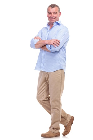 Foto de full length picture of a casual senior man standing with arms folded and looking at the camera. isolated on white background - Imagen libre de derechos